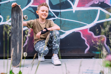 Boy with skateboard sits near graffiti painted wall