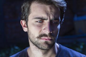 Depressed bearded man dark portrait