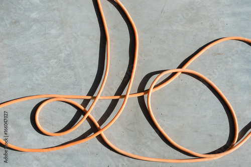 Abstract background - high angle view of orange electrical cord on concrete background with strong shadows