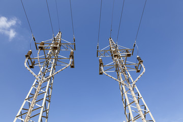 Electricity pylons against blue sky