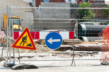Closed construction site with protective fence, work signs and barrier.