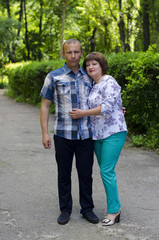A happy married couple are standing in an embrace against the background of a green fence from a bush.