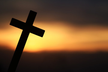Silhouette of a wooden cross in a beautiful sunset