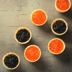 Black and red caviar tartlets, appetizer canapes on gray background, top view, toned