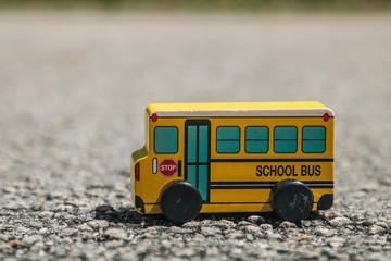 Yellow wooden school bus toy on the asphalt road