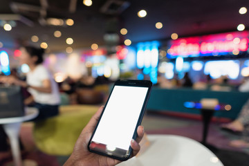 Hands holding blank white screen smart phone in front of the movie theatre, Hands holding smart phone to use for online booking ticket.