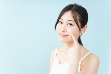 笑顔でスキンケアをする若い日本人女性