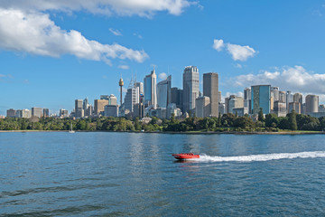 fast motor boat with splash and wake on Circular Quay with city scape and blue sky clouds background.