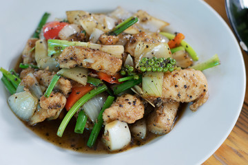 Close-up stir fried fish with black pepper in white plate