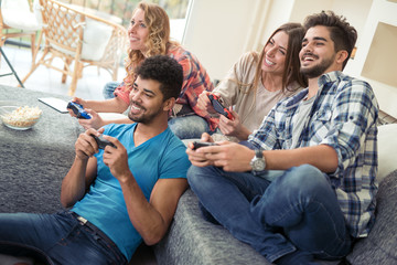 Friends  play video game with joystick at home in livingroom.