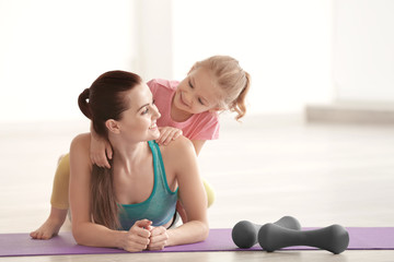 Mother and daughter in gym on light background
