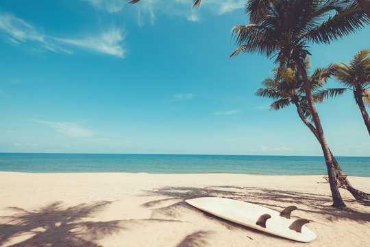 Surfboard on tropical beach in summer. landscape of summer beach and palm tree with sea, blue sky background. Vintage color tone
