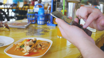 Client photographs liked the dish on a mobile phone. Take a photo of tom yam thai soup in a restaurant with mobile phone camera for social network while traveling in Thailand