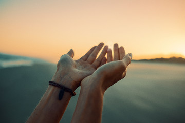 Hands reaching the sky in the sunset