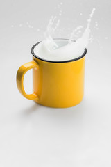 Yellow cup of fresh milk splash