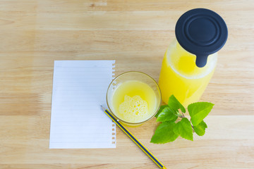 Note paper, Pineapple juice and green leaves placed on wooden table.