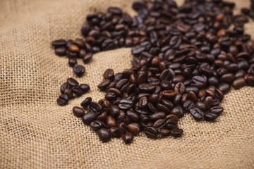 Fresh brown coffee beans on wooden background.