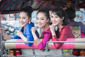 Beautiful Thai Girl in Thai Dress Traveling by Tuk Tuk in Bangkok,Are very happy.