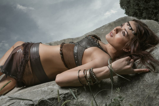 Young beautiful woman dressed in a leather wear looking like an amazon or warrior lying on a big stone. Dramatic beauty shot