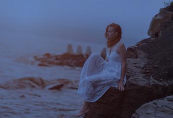 Redhead woman goes along the coast at night.