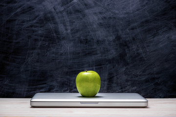 Apple on laptop on table in front of chalkboard.