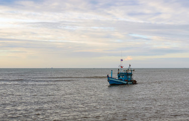 A lonely wooden fishing boat returns to the village after night catching at dawn
