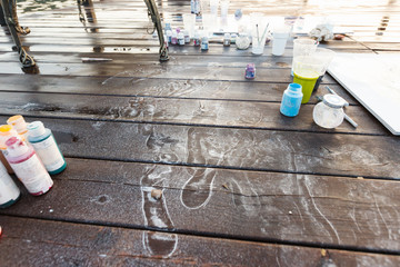 Young woman artist paints acrylic paint on nature on a wooden pier. Traces of her legs remained with paint on a wooden background