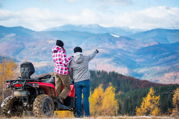 Rear view of young couple near red quad bike. Guy is showing something in distance to her girlfriend. Blurred autumn landscape mighty mountains and forests on background