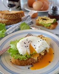 Egg poached on toast with cheese and lettuce leaves