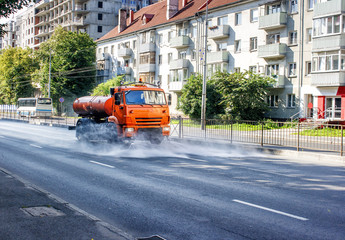 cleaning machine washing the city asphalt road with water spray
