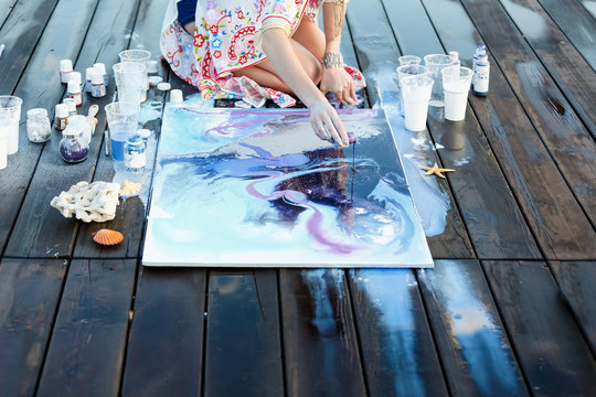Young beautiful artist woman is painting with acrylic paint on open air session. Art therapy on wooden pier at nature lake bay