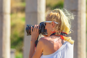 Profile of blonde caucasian woman photographer with professional camera in Ancient Messene, Archaeological Site, Peloponnese, Greece. Close up of female shotting a blurred ruins.Europe travel holidays