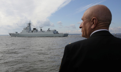 A man watches the Chinese destroyer Hefei during the Navy Day parade in Kronshtadt