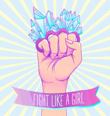 Fight like a girl. Woman's hand with crystal quartz brass knuckles. Fist raised up. Girl Power. Feminism concept.