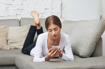 Woman with a mobile phone on couch