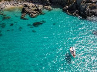 Vista aerea di una barca ormeggiata che galleggia su un mare trasparente. Immersioni relax e vacanze estive. Coste italiane, spiagge e rocce