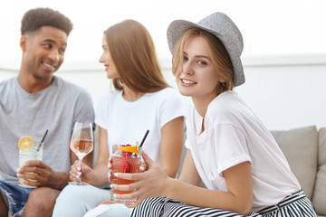 Portrait of youngsters sitting together at cozy sofa, drinking cocktails and wine having party. Mixed race people communicating with each other toasting by glasses. People, celebration, party concept