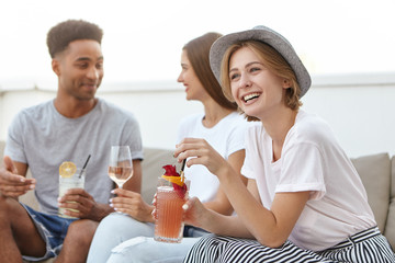 Beautiful cheerful female wearing hat, white blouse and stripped skirt holding cocktail listening to her interlocutor while sitting at sofa with her friends. Young people having party togehter