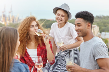 Team of young friendly people having summer party drinking wine and cocktails while standing at balcony having cheerful expressions resting together. Youth having fresh drinks during relaxation