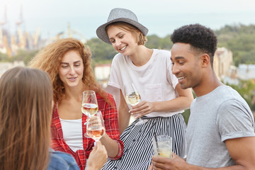Leisure, holidays, celebration and youth concept. Happy friends holding glasses with wine and cocktails celebrating their victory. Young people drinking at party outdoor. Group of multiracial people