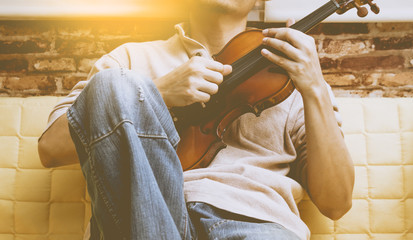 asian man enjoy playing violin on yellow seat for relaxation