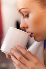 Closeup of woman drinking from white mug