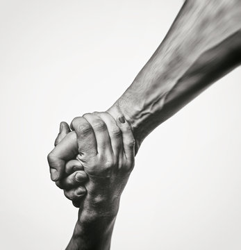 Concept of salvation. Black and white image of the hands of two people at the time of rescue (help).