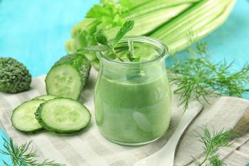 Jar of fresh vegetable juice on color background