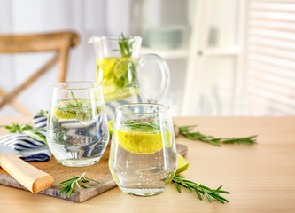 Glasses of fresh lemonade with rosemary on table