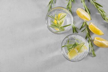Glasses of fresh lemonade with rosemary on grey background