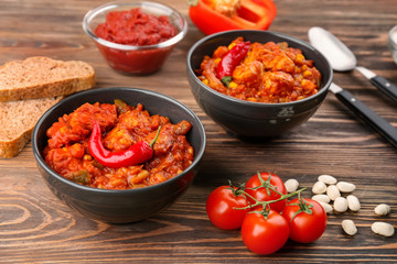 Two bowls with delicious chili turkey on wooden table