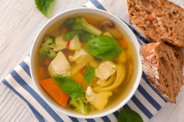 Bowl with delicious turkey soup and bread on table