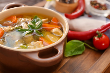 Casserole with delicious turkey soup on wooden board