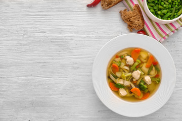 Plate with delicious turkey soup on wooden background